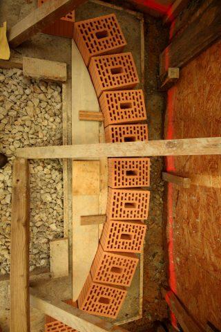 Um den Erdruck des Hanges besser abzufangen, mauern wir die Rückwand nun wie die Decke als Bogen. Die Holzschablone hilft, den Stich von 20 cm genau einzuhalten.