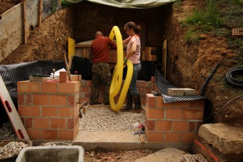 Zur Abdichtung wird die Mauer außenherum mit Bitumen eingeschmiert, dann kommt die Noppenbahn drumherum und dahinter das Drainagerohr. Was für ein Gefrickel. Diese gelbe Schlange ist sowas von widerspenstig!