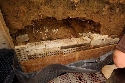 Nach dem Abbau der Stützkonstruktion wird der Blick auf die Erdrutschhöhle frei. Es ist nicht so schlimm wie befürchtet: nichts fällt uns entgegen, alles soweit stabil. Wir beginnen gleich mit dem Bau der Mauer hinter der Mauer.