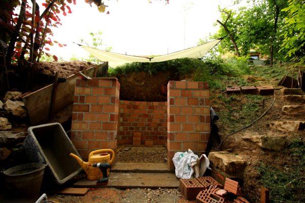"""Mauern im Trocknen trotz Regenwetter. Das Tarp leistet gute Dienste, und wird zum """"Baustellengegenstand des Monats"""" gekürt."""
