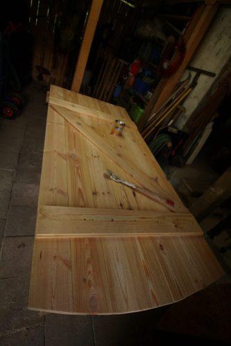 Eine Türe aus schwerem Eichenholz wäre natürlich sehr stilvoll gewesen ;-). Aber leichtes schneller wachsendes Fichtenholz tut´s auch und hält in den reingemauerten Angeln besser.