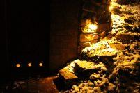 Weg zum Erdkeller durch Nacht und Schnee. Die drei erleuchteten Kreise sind die Lüftungsöffnungen in der Türe.